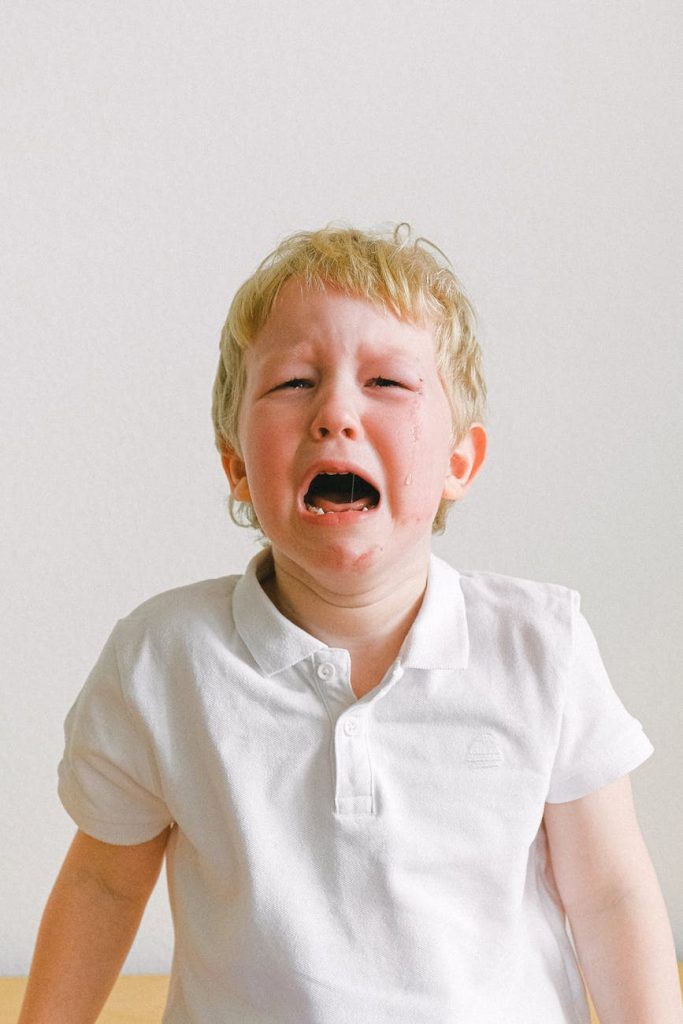 boy in white polo shirt crying